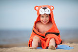 Cute little boy wearing tiger towel sitting at the beach