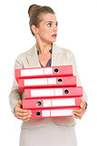 Surprised business woman holding stack of folders and looking on