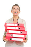Surprised business woman holding stack of folders and looking up