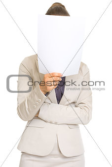 Business woman holding document in front of face