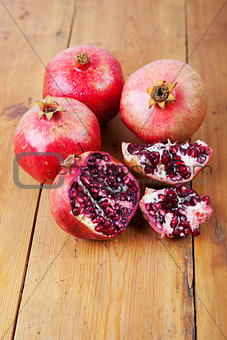 Four ripe pomegranate fruit on wooden surface