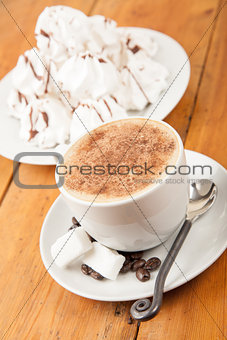 Fresh cappuccino with foam served with sugar cubes