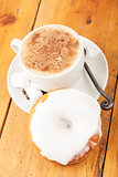 Fresh donut and cup of cappuccino on wooden table