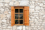 Wooden window and shutters in stone wall