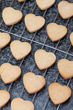 Heart shaped cookies fresh from the oven, cooling off on metal g
