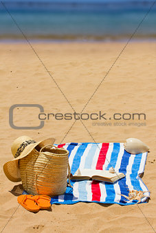 towel, sunbathing accessories and book
