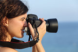 Attractive woman taking a photograph with her camera