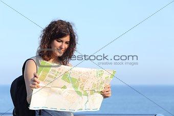 Beautiful tourist woman watching a city map