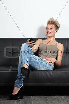 Fashion teenager listening to the music from a smartphone at home