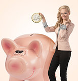 smiling business woman with big coin in piggy bank