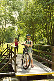 teenager relaxing on a bike trip on wooden bridge