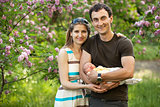 Young couple with newborn son outdoors in spring