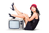 Lovely asian pinup girl posing on vintage tv set