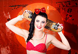Retro pinup girl holding old wooden skateboard
