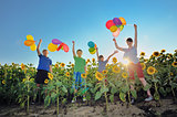 happy childrens jumping on meadow with balloons