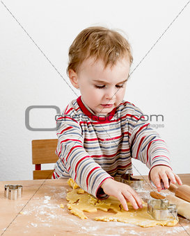 child at desk making cookies