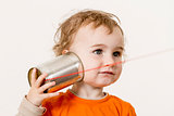 young child listening to tin can phone