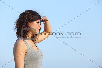 Attractive woman looking ahead with the hand in forehead