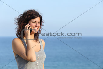 Beautiful woman talking on the mobile phone with the sea in the background