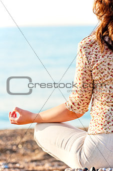 girl in lotus pose on the beach