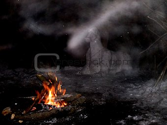 a snow figure in a winter forest at night by a bonfire