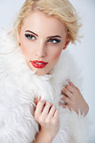 Stylish blonde woman posing in white fur