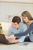Couple pointing and looking at laptop computer