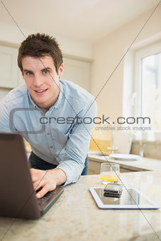 Man typing at the notebook with smartphone and tablet
