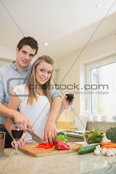 Couple chopping peppers and drinking wine