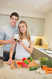 Man and woman cooking and clinking wine glasses
