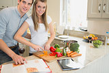 Woman cutting vegetables with man reading the cookery book