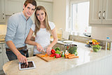 Man pointing on tablet pc with woman chopping peppers