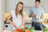 Man helping woman prepare the meal