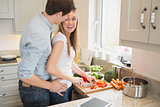 Man laughing with woman preparing vegetables