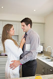 Woman fixing tie of husband before work