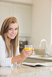Woman reading while drinking orange juice
