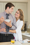 Man eats cereal while partner is embracing him