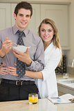 Man eating cereal while his wife is hugging him