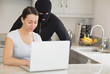 Woman using laptop while burgler is watching
