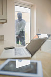 Burglar opening kitchen door and looking at laptop