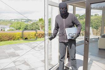 Burglar holding laptop