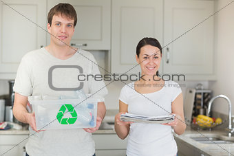 Couple holding recycling bin and newspapers