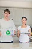Smiling couple holding newspapers and recycling bin