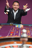 Man throwing chips onto roulette table
