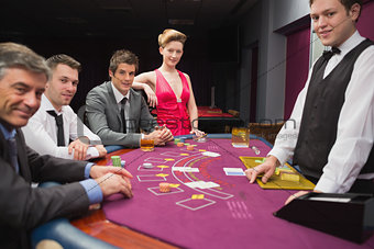 People sitting at blackjack table and smiling