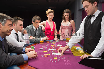 People looking at dealer dealing blackjack cards