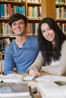 Two happy students in a library