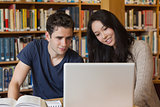 Two students learning in a library with a laptop