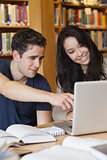 Two students learning on the laptop in a library