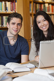 Two students learning with a laptop in a library